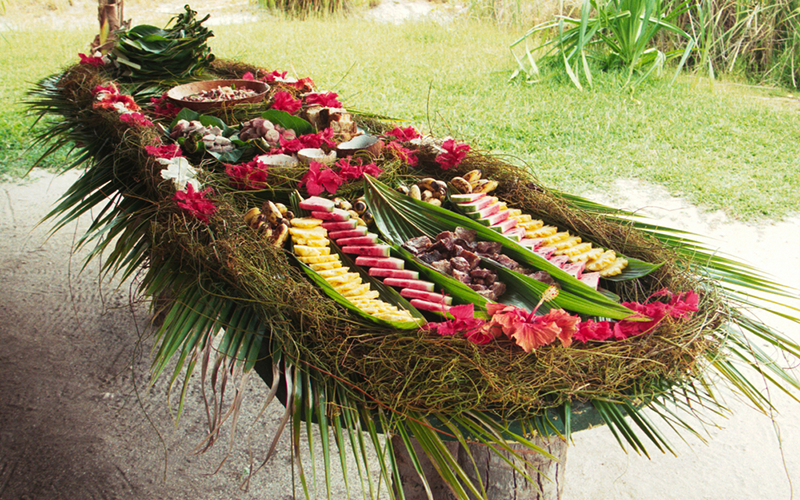 During meals, local dishes are presented on banana leaves and decorated with flowers. A table prepared for the midday meal on Bora Bora, French Polynesia.<br/><small>©Shutterstock/Christophe Testi</small>